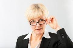 Зрелая коммерсантка смотря через eyeglasses стоковые изображения rf