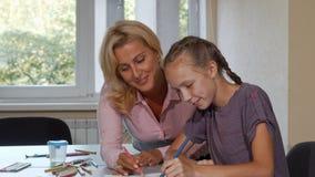 Зрелая красивая женщина наслаждаясь рисовать с ее маленьким студентом акции видеоматериалы