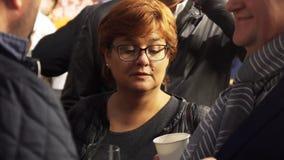 Зрелая красная с волосами женщина нося стекла имеет разговор с 2 людьми акции видеоматериалы