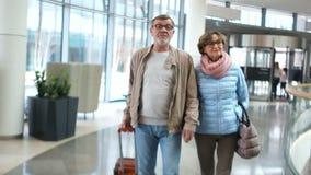 Зрелая прогулка женщины и человека через крупный аэропорт Человек имеет чемодан в его руках Романтичные пары перемещения  акции видеоматериалы
