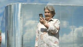 Зрелая старуха говорит используя умный телефон outdoors акции видеоматериалы