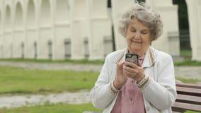 Зрелая старуха держит серебряный умный телефон outdoors видеоматериал