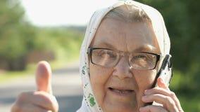 Зрелая старуха показывает большие пальцы руки вверх по знаку outdoors видеоматериал