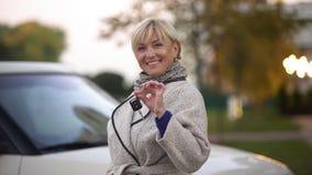 Зрелая успешная женщина усмехаясь и держа ключи нового роскошного автомобиля, настоящего момента стоковое изображение rf