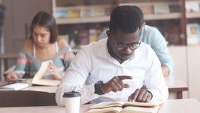 Зрелища Афро-американского мужского студента колледжа нося подготавливая для экзаменов в библиотеке, читая книгу акции видеоматериалы