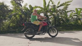 Зрелое катание мотоциклиста человека на мотоцикле на дороге сельской местности на тропическом ландшафте пальм Путешествовать стар акции видеоматериалы
