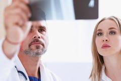 Зрелое мужское владение доктора в руке и взгляд на фотографии рентгеновского снимка Стоковое Фото