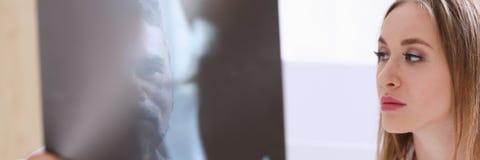 Зрелое мужское владение доктора в руке и взгляд на фотографии рентгеновского снимка Стоковые Изображения