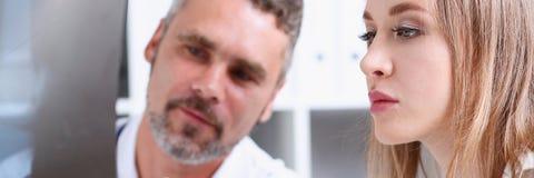 Зрелое мужское владение доктора в руке и взгляд на фотографии рентгеновского снимка Стоковые Изображения RF