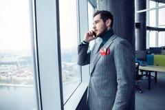 Зрелое положение бизнесмена внутри офисного здания и сотового телефона использования Окно человека готовя и говорить на черни стоковая фотография