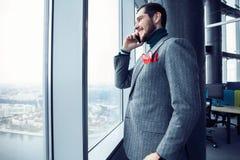Зрелое положение бизнесмена внутри офисного здания и сотового телефона использования Окно человека готовя и говорить на черни стоковая фотография rf