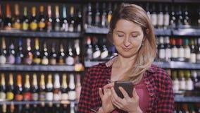 Зрелое положение женщины в гипермаркете со смартфоном в руках видеоматериал