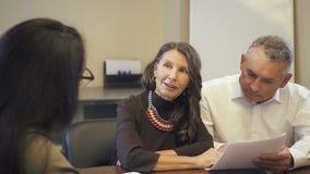 Зрелое чтение пар и обсуждать контракт ипотеки в имущественном агентстве недвижимости видеоматериал