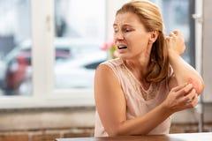 Зрелое чувство женщины больное имеющ сыпь и царапины на теле стоковое фото rf