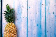 Зрелые ананасы над голубым деревянным столом стоковое фото rf