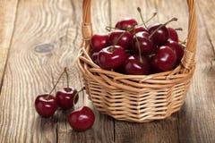 Зрелые вишни в корзине на старой доске Стоковые Изображения