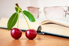 Зрелые вишни на предпосылке открытой книги Пролом во время re стоковые изображения