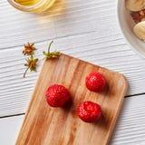 Зрелые клубника и черенок клубники на деревянной доске на белом деревянном столе Взгляд сверху Стоковые Изображения RF