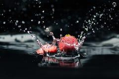 Зрелые клубники падая в воду Стоковые Изображения