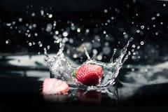 Зрелые клубники падая в воду Стоковое Изображение RF