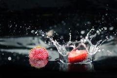 Зрелые клубники падая в воду Стоковая Фотография RF