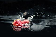 Зрелые клубники падая в воду Стоковые Фотографии RF