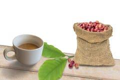 Зрелые кофейные зерна в мешке на белой предпосылке Стоковые Изображения