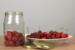 Зрелые красные вишни на белой плите на деревянном столе Домодельный опарник вишни Белая предпосылка Стоковое Изображение RF