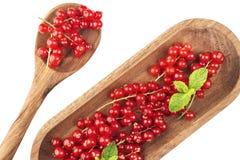 Зрелые красные смородины на деревянной плите с ложкой на белом backgroun Стоковые Изображения