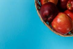 Зрелые красные яблоки в корзине на голубой предпосылке стоковая фотография rf