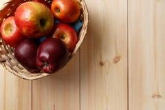 Зрелые красные яблоки в корзине на яркое деревянном стоковые изображения rf