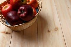 Зрелые красные яблоки в корзине на яркой деревянной предпосылке стоковое изображение rf
