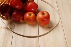Зрелые красные яблоки в корзине на яркой деревянной предпосылке стоковое фото rf
