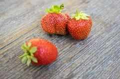 Зрелые 3 красных сладостных клубники на деревянном столе, Стоковое Изображение