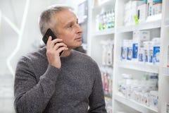 Зрелые лекарства приобретения человека на аптеке стоковое фото rf