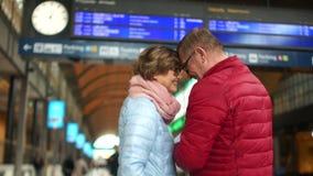 Зрелые пары на билетах проверок железнодорожного вокзала с расписанием Человек целует женщину на лбе и они идут сток-видео