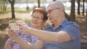 Зрелые пары принимая фото selfie сидя на парке стенда сток-видео