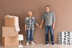 Зрелые пары с двигая коробками и пожитки на новом доме стоковые изображения