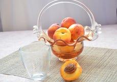 Зрелые персики и стекло сока на таблице, отрезанного персика, красивой вазы в форме предпосылки корзины Стоковые Изображения RF