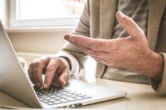 Зрелые руки бизнесмена работая на компьтер-книжке конец вверх Стоковые Фото