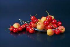 Зрелые свежие абрикосы и вишни в прозрачной стеклянной вазе дальше Стоковое Изображение