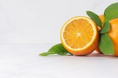 Зрелые сочные желтые половинные апельсины с свежими зелеными листьями на белой деревянной доске, крупном плане, космосе экземпляр Стоковые Изображения