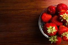 зрелые сочные красные клубники в стеклянном шаре на деревянном столе Стоковая Фотография RF