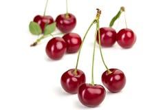 Зрелые сочные ягоды вишни с листьями на белой таблице Стоковая Фотография