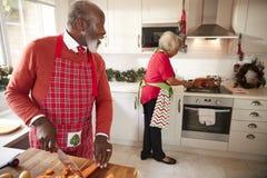 Зрелые черные пары подготавливая рождественский ужин, человека прерывая овощи на переднем плане, поворачивающ к его партнеру кото стоковое фото