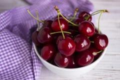 Зрелые ягоды вишни в белой плите на ягодах белых деревянных вишни backgrounRipe в белой плите на белой деревянной предпосылке, Стоковая Фотография RF