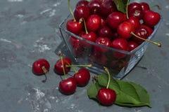 зрелые ягоды вишни в стеклянной вазе на серой конкретной предпосылке Стоковое Фото