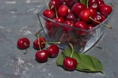 зрелые ягоды вишни в стеклянной вазе на серой конкретной предпосылке Стоковое Изображение