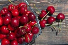 зрелые ягоды вишни в стеклянной вазе на темном деревянном конце-вверх предпосылки Стоковые Фото