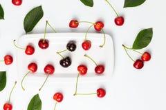 Зрелые ягоды вишни и листья вишни на белой плите изолировали к Стоковое Изображение RF